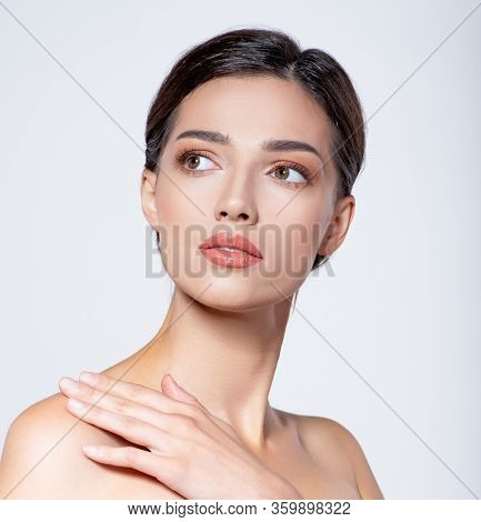 Portrait of beautiful  brunette girl which touching her fresh face. Beautiful face of young woman with health fresh skin.  Beautiful face of young adult woman with clean fresh skin. Skin care.