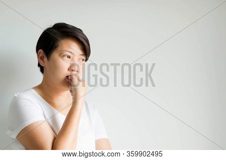 A Side Portrait Of An Absent-minded Woman Feeling Nervous Anxious; Expression By Biting Nail Of The