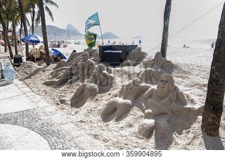 Rio De Janeiro, Brasil- March 05, 2020: Sand Sculptures On Copacabana Beach. People Go About Their B
