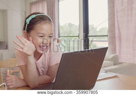 Mixed Race Young Asian Girl Making Facetime Video Calling With Laptop At Home, Using Zoom Learning O