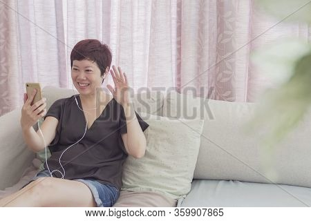 Portrait Of Healthy Middle Aged 40s Asian Woman Making Facetime Video Calling With Smartphone At Hom