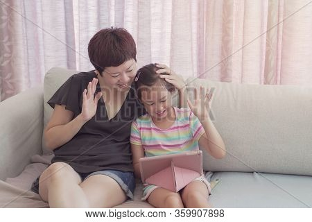 Mixed Race Young Asian Girl And Her Mother Making Facetime Video Calling With Laptop At Home, Using