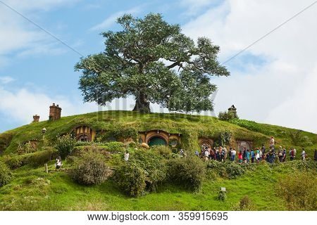 MATAMATA, NEW ZEALAND - CIRCA 2016: Movie set for the Lord of The Rings and The Hobbit. Bilbo Baggins house with the notable tall oak tree above it. Guided tour going on