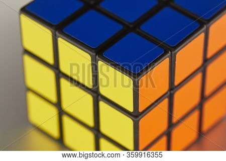BUDAPEST, HUNGARY - CIRCA 2019: Solved Rubik's cube logic game on shiny metal surface evenly lit from all sides