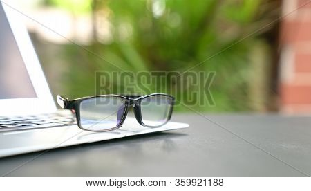 Spectacles On Top Of Computer Laptop With Home And Green Nature Background. Copy Space. Work Remotel