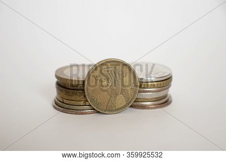 Fifty Piastres Coin. Coin On A White Background Stands Next To Other Coins Piled In A Stack