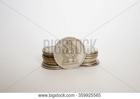 Coin Worth Two Rupees. A Coin On A White Background Stands Vertically In A Row With Other Coins Pile