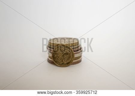 Polish Coin One Grosz. A Coin On A White Background Stands Vertically Next To Other Coins Piled In A