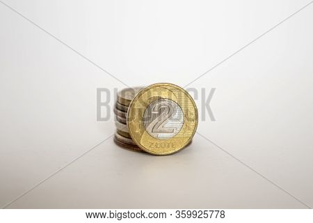 A Polish Coin Worth Two Zloty. Coin On A White Background Stands Vertically Next To Other Coins Pile