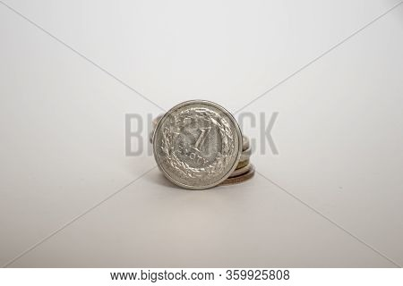 A Polish Coin Worth One Zloty. A Coin On A White Background Stands Vertically Next To Other Coins Pi