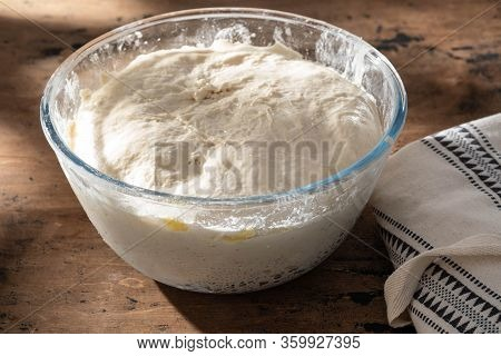 Bowl Of Fresh Raw Dough On Wooden Background