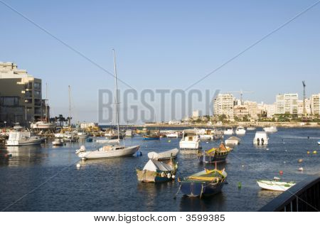 malta maltese luzzu classic fishing boats in harbor st. julian's paceville sliema over development condominiums poster