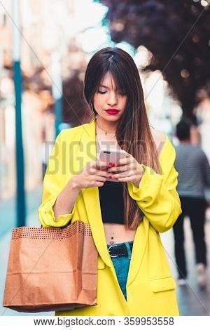 Woman Shopping And Looking At The Smartphone On The Street