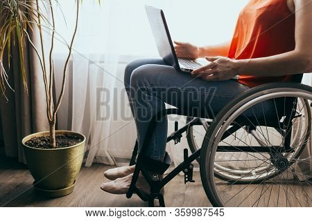 Woman In A Wheelchair At Home With A Laptop On Her Lap, Hand Close Up, Unrecognizable Man.