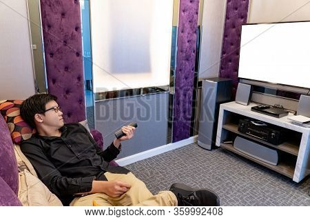 Asian Happy Man Using Remote Controller While Watching Tv Sitting On Sofa In Living Room. Domestic L