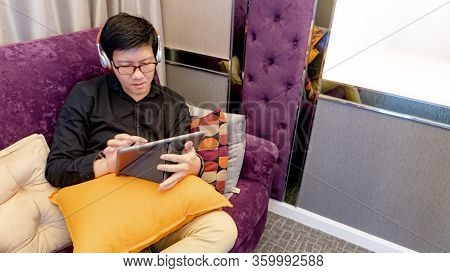 Asian Man Sitting On Sofa Using Digital Tablet In Living Room. Working At Home, Watching Live Stream