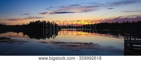 Daybreak Reflections On A Calm Lake. Wide Format Image.
