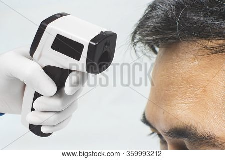Medical Infrared Thermometer In A Hand Of The Doctor Measuring The Temperature Of The Asian Male Pat