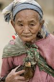 Asia old woman with chicken in a village in Laos poster