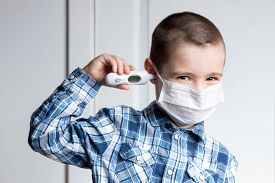 Young Boy With Sore Eyes In A Medical Mask Measures The Temperature Of A Thermometer In His Ear. Med