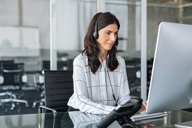 Mature secretary working in call center with headset. Confident telephone operator in modern office working on computer while taking calls. Smiling customer support operator at work with copy space.