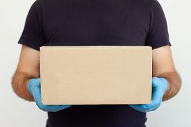 Delivery Man Holding Cardboard Boxes In Medical Rubber Gloves. Copy Space. Fast And Free Delivery Tr