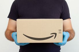 Amazon Delivery. Delivery Man Holding Cardboard Boxes In Medical Rubber Gloves. Copy Space. Fast And