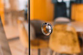 Round Metal Doorknob In The Glass Door