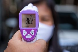 Female Doctor Checking Temperature Using Infrared Thermometer,tool For Detect Coronavirus Or Covid-1