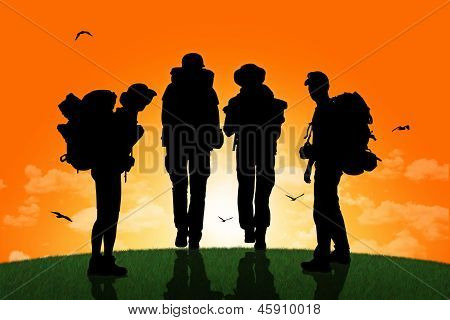 Group Of Backpackers Walking On A Top Of A Hill At Sunset