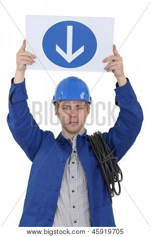 Electrician holding a one way sign