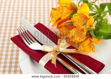 Festive dining table setting with flowers on checkered background