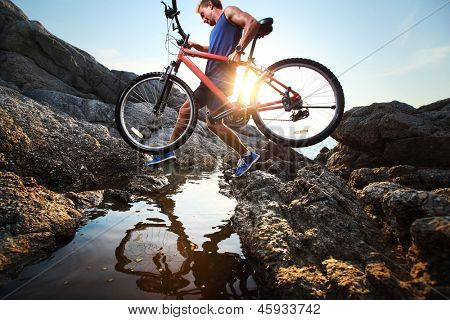 Young athlete crossing rocky terrain with bicycle in his hands
