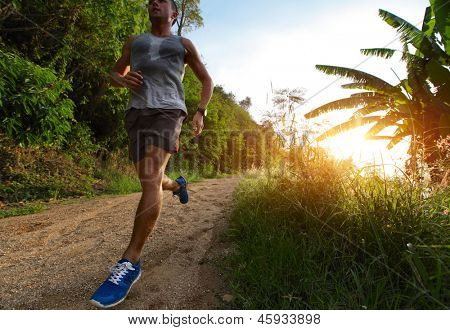 Young man running on a rural road during sunset
