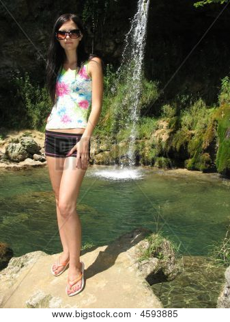 Young Woman Standing At The Waterfall