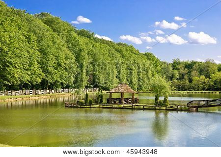 Wooden arbour on green lake