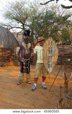 Zulu Chief posing with tourist in Shakaland Zulu Village, South Africa