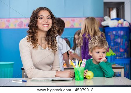 Portrait of beautiful teacher with bored boy sitting at desk in classroom