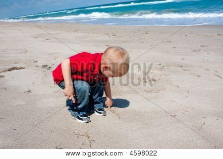男孩在沙子里的绘图