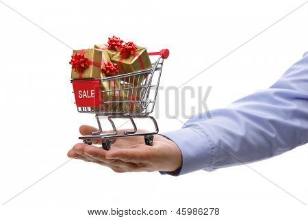 Shopping cart full of gold gift boxes and red sale sign