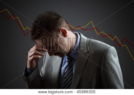 Depressed businessman in economic crisis with line graph showing negative trend