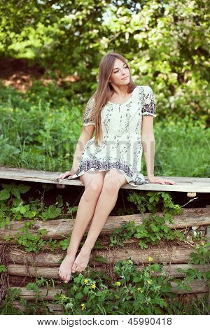 Girl In A Summer Dress Sitting And Relaxing