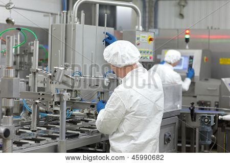 two workers in uniforms at production line in plant