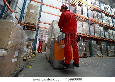 Logistik - Warenlieferung - zwei Arbeitnehmer arbeiten im Lagerhaus mit Gabelstapler-loader