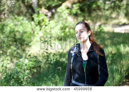 Young Woman Hikes Through Shady Forest