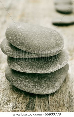 a stack of balanced stones on an old wooden surface