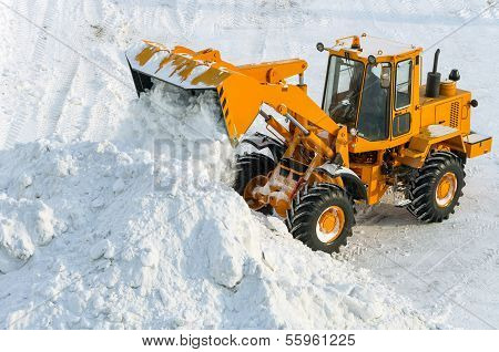Excavator is clearing the streets after snow drifts. poster