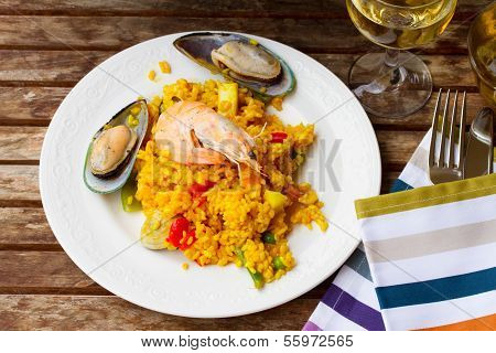 Paella served in white plate on wooden table