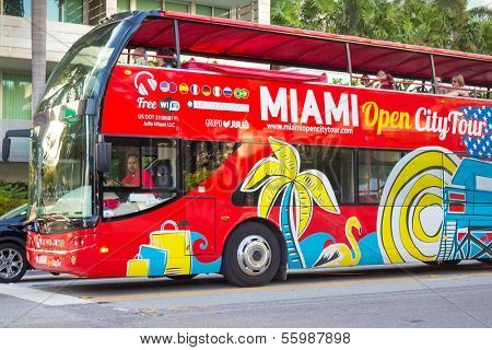 MIAMI,US - NOVEMBER 24,2013:Open deck sightseeing bus at Miami Beach. International tourists make up 48% of all visitors and contribute at least $2.9 billion to the Miami economy