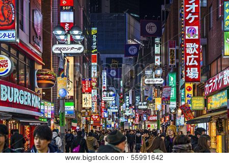 TOKYO, JAPAN - DECEMBER 24, 2012: Crowds walk through Shibuya. The district is a youth and fashion center.